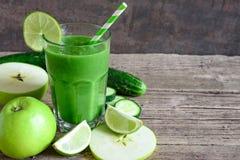 在一块玻璃的绿色圆滑的人用菠菜、苹果、黄瓜和石灰与秸杆 戒毒所饮料 库存图片