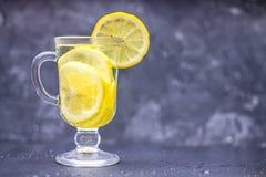 在一块玻璃的自创柠檬水与在灰色具体背景的把柄 浇灌与切片在黑暗的背景的柠檬 免版税图库摄影
