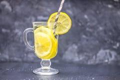在一块玻璃的自创柠檬水与在灰色具体背景的把柄 浇灌与切片在黑暗的背景的柠檬 免版税库存照片