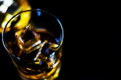 在一块玻璃的苏格兰威士忌酒与冰块,金黄颜色威士忌酒 免版税库存图片