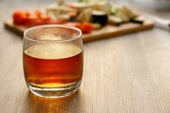 在一块玻璃的茶在一张木桌上 免版税库存照片