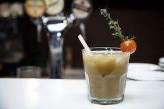 在一块玻璃的菜鸡尾酒与管装饰了用与分支的一个蕃茄以一个模糊的酒吧为背景 库存照片