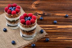 在一块玻璃的蓝莓和莓冷甜点在土气b 免版税图库摄影