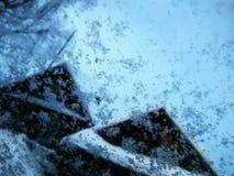 在一块玻璃的雪花反对蓝天和房子 免版税库存图片