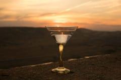 在一块玻璃的马蒂尼鸡尾酒反对与山的日落背景 在日落时间的俱乐部饮料 免版税库存照片