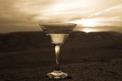 在一块玻璃的马蒂尼鸡尾酒反对与山的日落背景 在日落时间的俱乐部饮料 免版税图库摄影