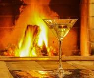 在一块玻璃的马蒂尼鸡尾酒在壁炉前,在豪宅,冬天假期, 库存图片