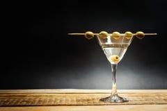 在一块玻璃的马蒂尼鸡尾酒饮料用在棍子的橄榄 免版税库存照片