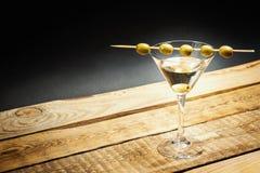 在一块玻璃的马蒂尼鸡尾酒饮料用在棍子的橄榄 库存图片