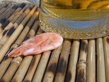在一块玻璃附近的虾用啤酒 免版税库存图片