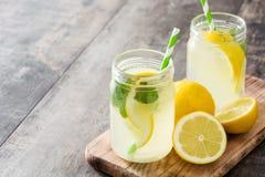 在一块瓶子玻璃的柠檬水饮料在木头 库存图片