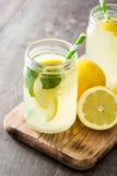 在一块瓶子玻璃的柠檬水饮料在木头 图库摄影