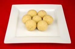 在一块白方块板材的圆的印地安laddu甜点 库存图片