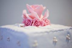 在一块白色婚宴喜饼的桃红色小杏仁饼花 免版税库存图片