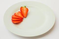 在一块白色板材切和安排的新鲜的有机草莓 免版税库存图片