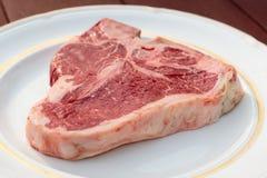 在一块白色板材的丁骨牛排 免版税库存图片