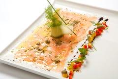 在一块白色板材的三文鱼carpaccio 海鲜Carpaccio -三文鱼Carpaccio 库存照片