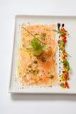 在一块白色板材的三文鱼carpaccio 海鲜Carpaccio -三文鱼Carpaccio 库存图片
