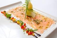 在一块白色板材的三文鱼carpaccio 海鲜Carpaccio -三文鱼Carpaccio 图库摄影