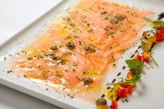 在一块白色板材的三文鱼carpaccio 海鲜Carpaccio -三文鱼Carpaccio 免版税库存照片
