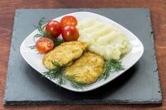在一块白色板材的两个水多的油煎的肉小馅饼用西红柿 库存照片