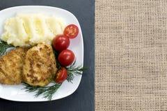 在一块白色板材的两个水多的油煎的肉小馅饼用西红柿 免版税库存图片