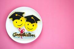 在一块白色板材的五颜六色的毕业曲奇饼 库存图片