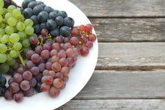在一块白色板材的五颜六色的葡萄在一张土气木桌上 免版税库存照片