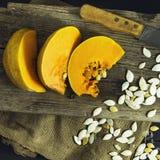 在一块白色板材的切的成熟南瓜有种子和一把木匙子的 收获秋天 库存照片