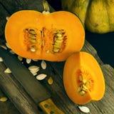 在一块白色板材的切的成熟南瓜有种子和一把木匙子的 收获秋天 免版税库存图片