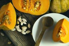 在一块白色板材的切的成熟南瓜有种子和一把木匙子的 收获秋天 免版税库存照片