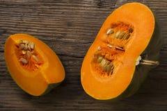 在一块白色板材的切的成熟南瓜有种子和一把木匙子的 收获秋天 免版税图库摄影