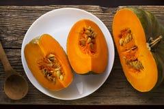 在一块白色板材的切的成熟南瓜有种子和一把木匙子的 收获秋天 库存图片