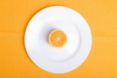 在一块白色板材的切的成熟开胃桔子在一黄色napki 库存照片