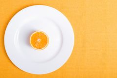 在一块白色板材的切的成熟开胃桔子在一黄色napki 免版税图库摄影
