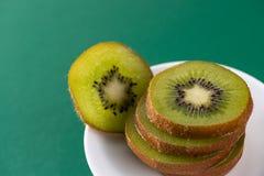 在一块白色板材的可口新鲜的被切的猕猴桃在绿色背景 库存图片