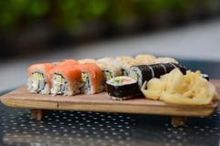 在一块白色板材的可口被分类的寿司在绿色背景 库存照片