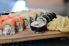 在一块白色板材的可口被分类的寿司在绿色背景 库存图片