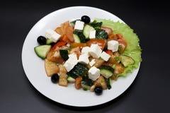 在一块白色板材的希腊沙拉在黑背景 能使用作为照片为餐馆菜单,小餐馆 欧洲,地中海c 库存图片