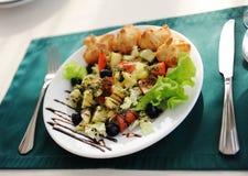 在一块白色板材的希腊沙拉 服务在与一张绿色桌布的一张桌上在餐馆 库存照片