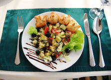 在一块白色板材的希腊沙拉 服务在与一张绿色桌布的一张桌上在餐馆 免版税库存照片
