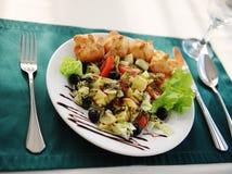 在一块白色板材的希腊沙拉 服务在与一张绿色桌布的一张桌上在餐馆 免版税图库摄影