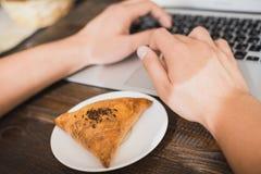 在一块白色板材的开胃samsa,在膝上型计算机旁边 水平的框架 免版税库存照片