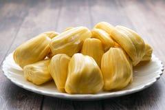 在一块白色板材的新波罗蜜切片 成熟甜黄色的波罗蜜 素食主义者,素食主义者,未加工的食物 异乎寻常的热带水果-孤立 免版税库存照片