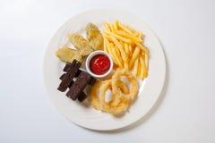 在一块白色板材的新鲜的啤酒快餐分类 炸薯条、油煎方型小面包片和夏南瓜和洋葱圈 库存图片