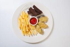 在一块白色板材的新鲜的啤酒快餐分类 炸薯条、油煎方型小面包片和夏南瓜 库存照片