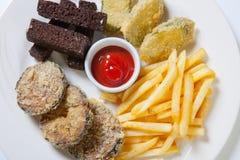 在一块白色板材的新鲜的啤酒快餐分类 炸薯条、油煎方型小面包片和茄子 免版税库存图片