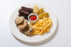 在一块白色板材的新鲜的啤酒快餐分类 炸薯条、油煎方型小面包片和茄子 免版税图库摄影