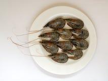 在一块白色板材的新鲜的未煮过的国王大虾在白色背景 纤巧,鲜美和健康海鲜,关闭,顶视图 免版税库存图片