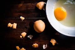 在一块白色板材的新鲜的鸡蛋在一个木地板上 免版税库存图片